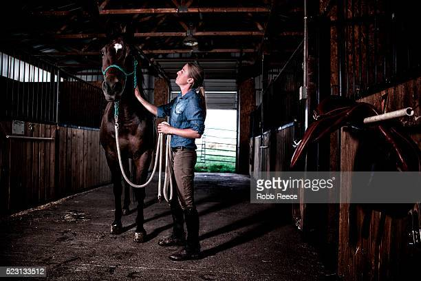 woman with horse in stables - robb reece stockfoto's en -beelden