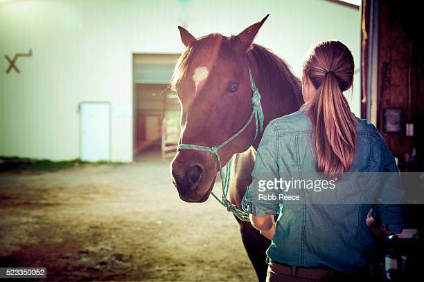 woman with horse inside stable doorway - robb reece stockfoto's en -beelden