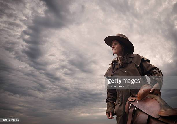 Woman with horse saddle and hat & stormy sky