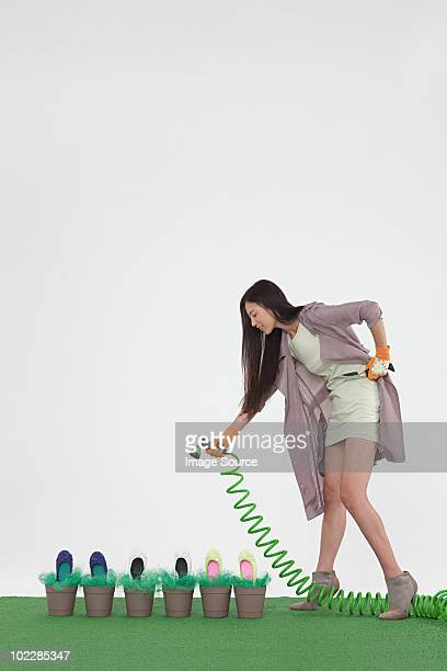 Woman with hosepipe and shoes in flower pots