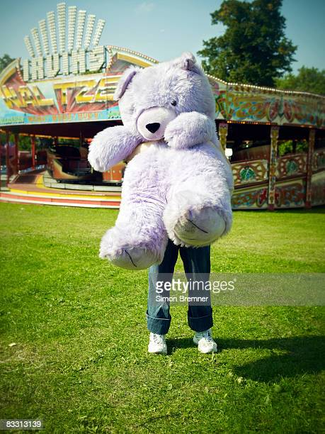 Woman with huge teddy bear at funfair