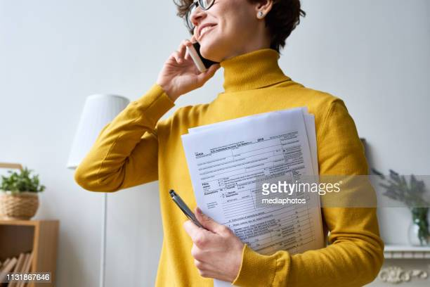 woman with individual income tax return form - filing documents stock pictures, royalty-free photos & images