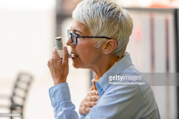 喘息発作に苦しむ吸入器を持つ女性 - 状態 ストックフォトと画像