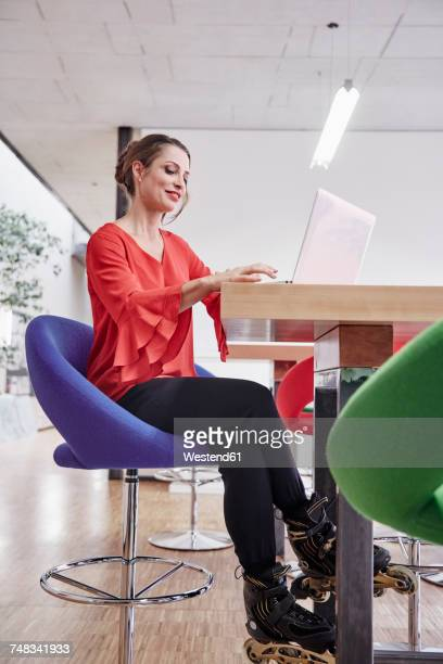 woman with inline skates using laptop in office - inline skating stock pictures, royalty-free photos & images