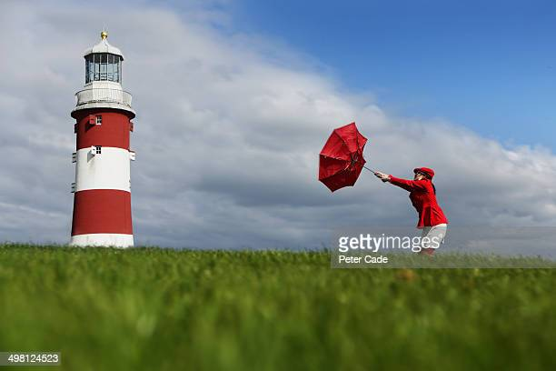 woman with inside out umbrella next to lighthouse - gale stock photos and pictures