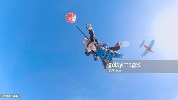 woman with instructor in free fall. - diving to the ground stock pictures, royalty-free photos & images