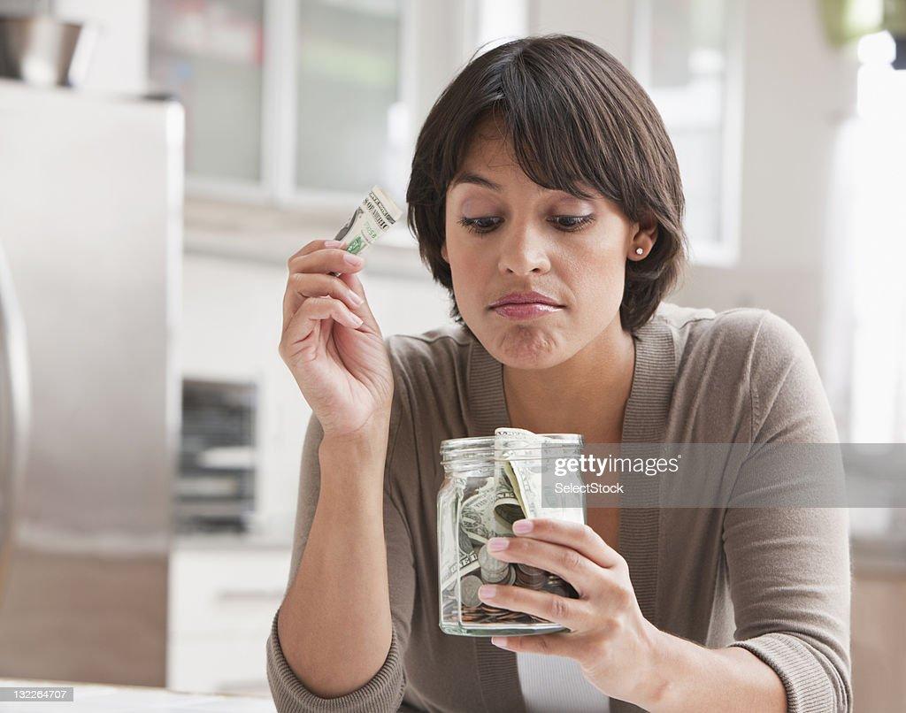 Woman with jar of cash : Bildbanksbilder