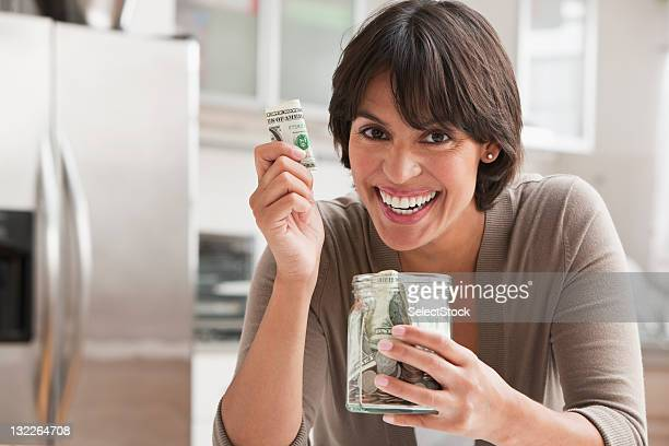 woman with jar of cash - 40 44 jaar stock pictures, royalty-free photos & images