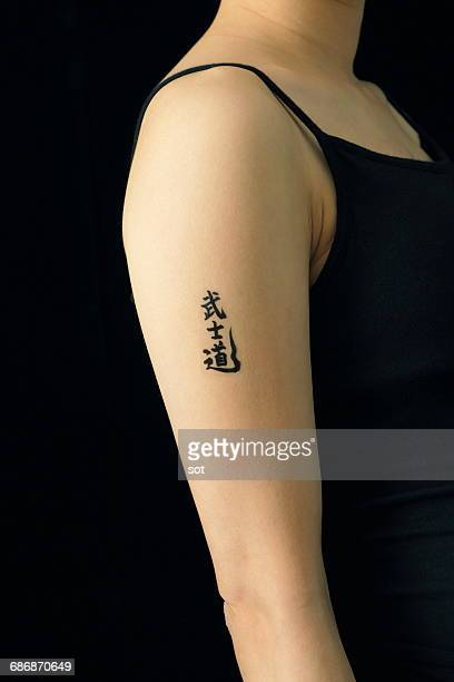 Woman with kanji tattoo seal on arm,close up