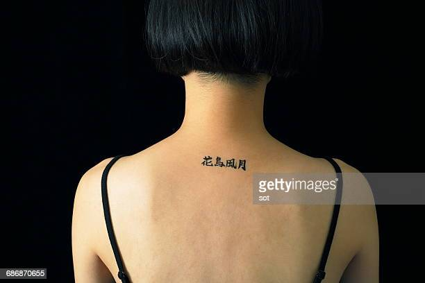 woman with kanji tattoo seal on neck - scrittura non occidentale foto e immagini stock