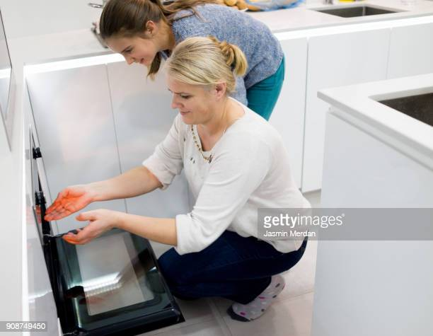 Woman with kids in kitchen making sweet