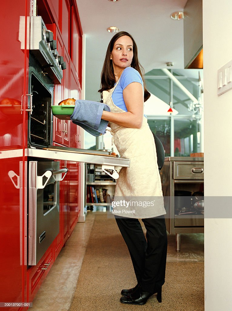 Woman with kitchen mitts taking food out of oven : Stock Photo