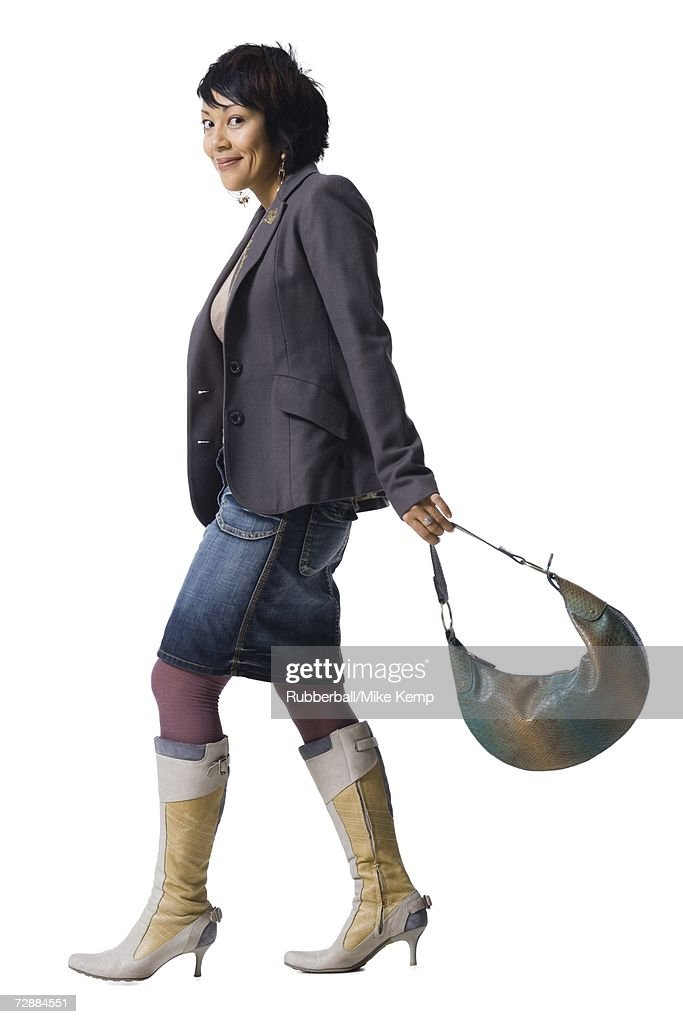 ef087711eca Woman With Knee High Boots And Handbag Stock Photo - Getty Images