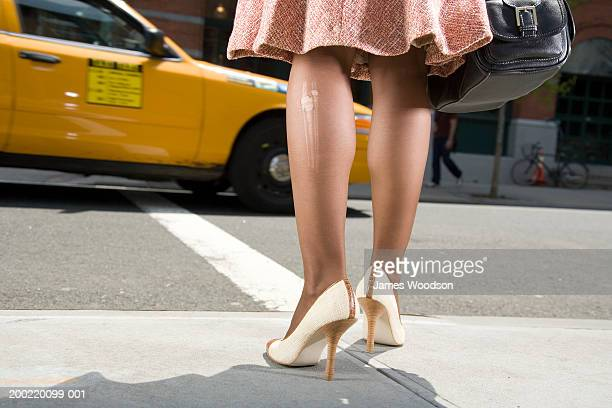 woman with laddered stockings standing at roadside, low section - femme bas photos et images de collection