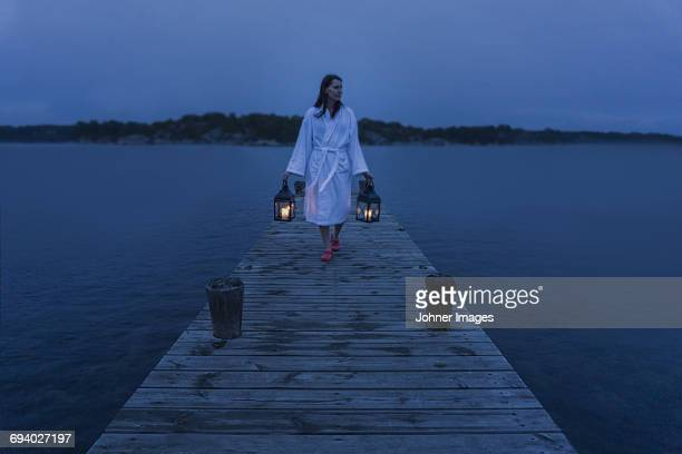 A woman with lantern on jetty