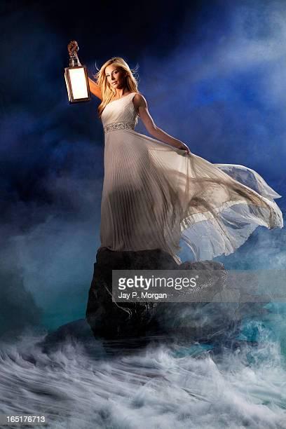 woman with lantern on rock at sea - mitologia greca foto e immagini stock