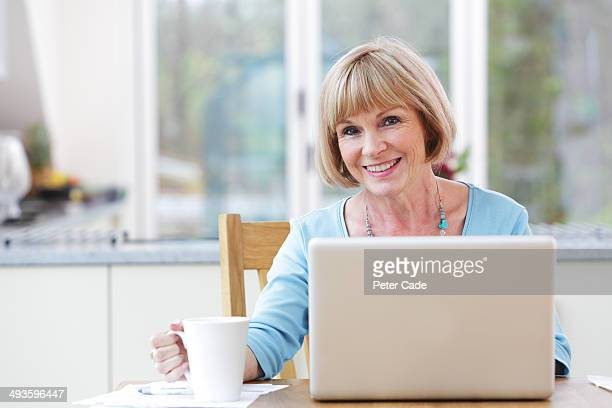 Woman with laptop and drink smiling