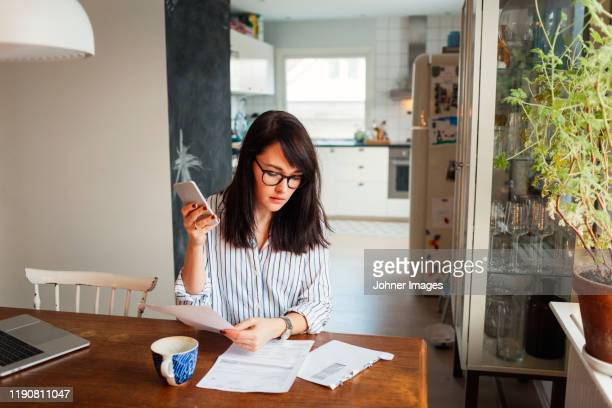 woman with laptop and smartphone in dining room - financial bill stock pictures, royalty-free photos & images