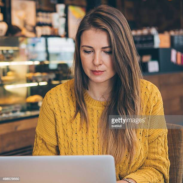 Woman with laptop at cafe.