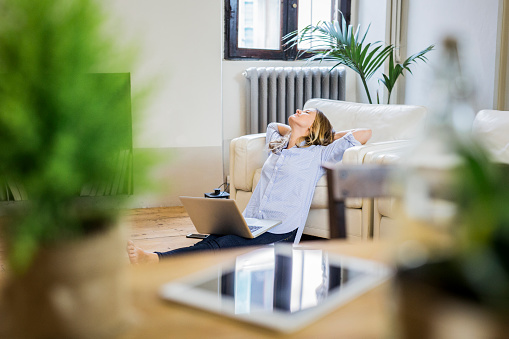 Woman with laptop at home leaning back - gettyimageskorea
