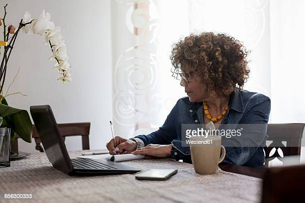 Woman with laptop at home writing in booklet