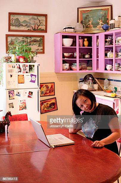 woman with laptop at kitchen table - jessamyn harris stock pictures, royalty-free photos & images