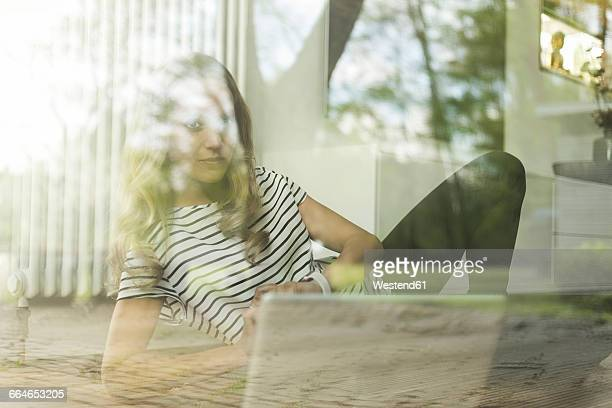 Woman with laptop behind windowpane