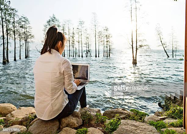 Woman with laptop by the lake