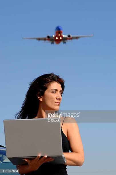 Woman with Laptop Computer and Airliner Flying Overhead