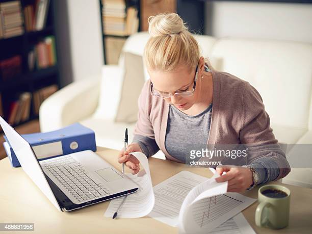 Woman with laptop doing paper work at her desk