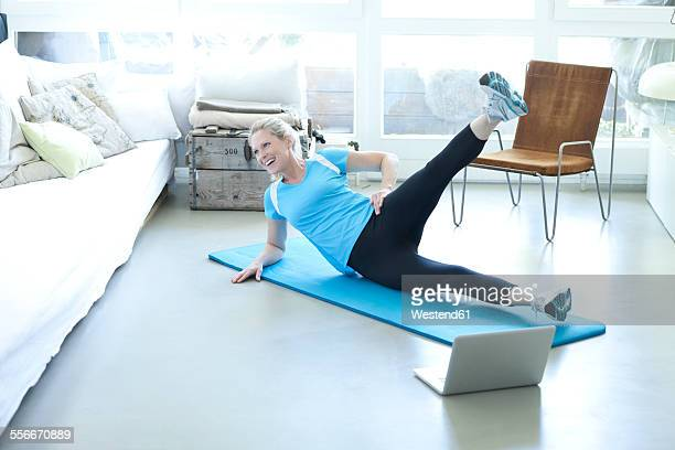Woman with laptop exercising on gym mat in living room
