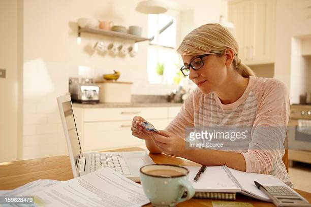 Woman with laptop holding credit card