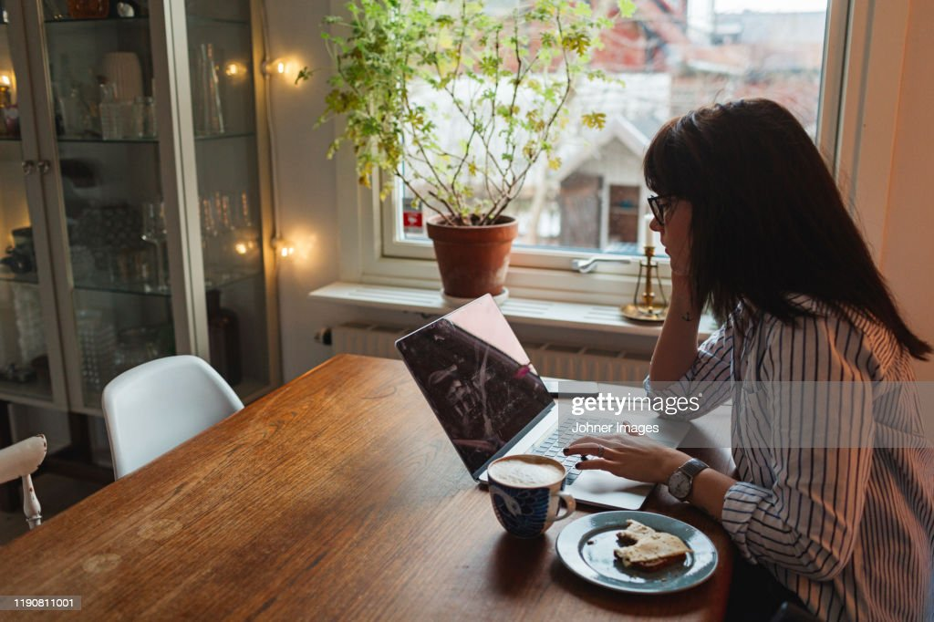 Woman with laptop in dining room : Stockfoto