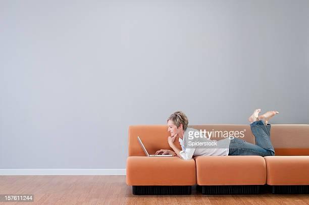 mulher com o laptop na sala vazia - simplicidade - fotografias e filmes do acervo