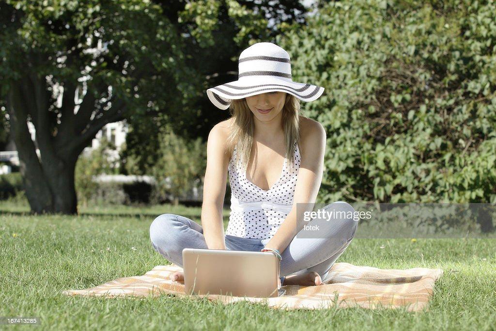 Femme avec un ordinateur portable dans le parc : Photo