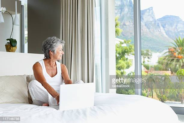 Woman with laptop looking away