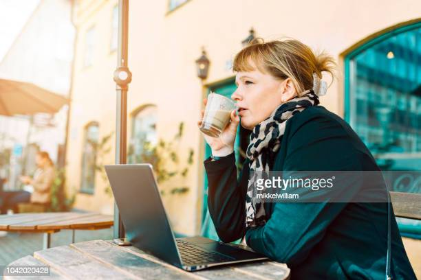 Woman with laptop pc drinks coffee at outdoor cafe