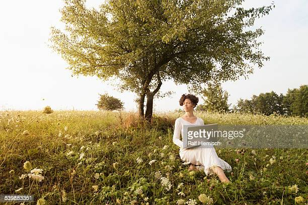 Woman with laptop relaxing on field