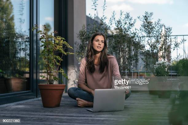 Woman with laptop sitting on balcony