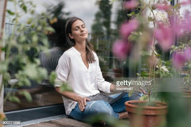 woman with laptop sitting on balcony - gelassene person stock-fotos und bilder