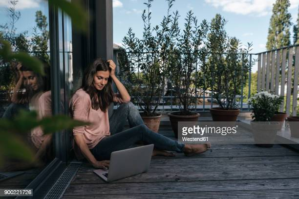 woman with laptop sitting on balcony - alleen mid volwassen vrouwen stockfoto's en -beelden