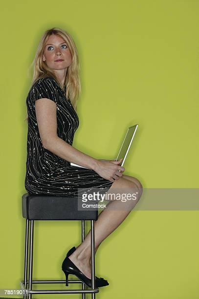 Woman with laptop sitting on stool