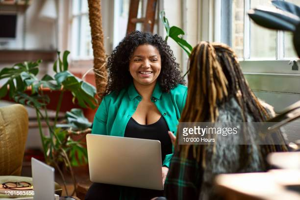woman with laptop talking to colleague on sofa - new business stock pictures, royalty-free photos & images