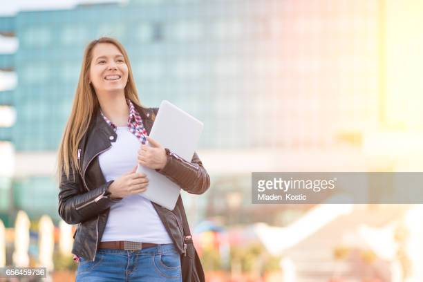 Woman with laptop waiting for someone outside office building