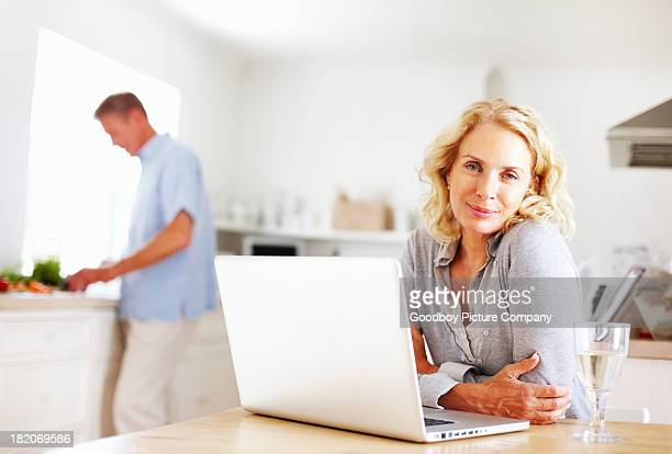 Woman with laptop while man cutting vegetables in background
