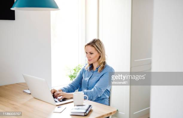 woman with laptop working at home - mid adult stock pictures, royalty-free photos & images