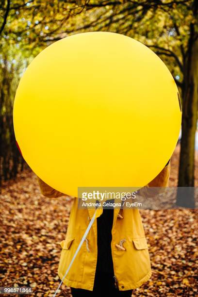 Woman With Large Yellow Balloon Standing At Park During Autumn