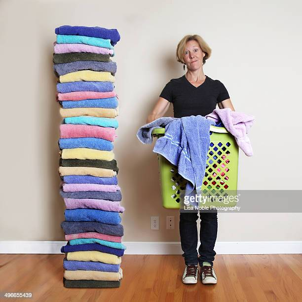 Woman with laundry basket next to stacked towels