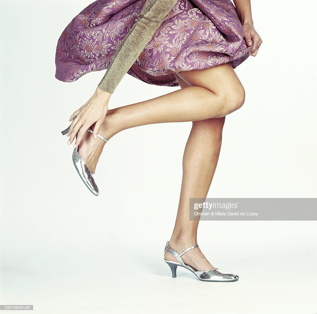 Woman with leg raised, reaching for heeled shoe, low section : Stock Photo