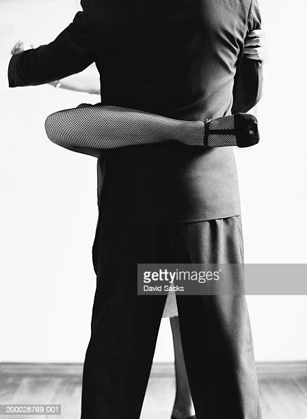 Woman with leg wrapped around man's waist, mid section (B&W)